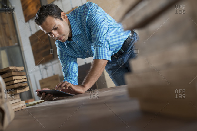 A young man in a workshop which uses recycled and reclaimed lumber to create furniture and objects. Using a digital tablet in his work.