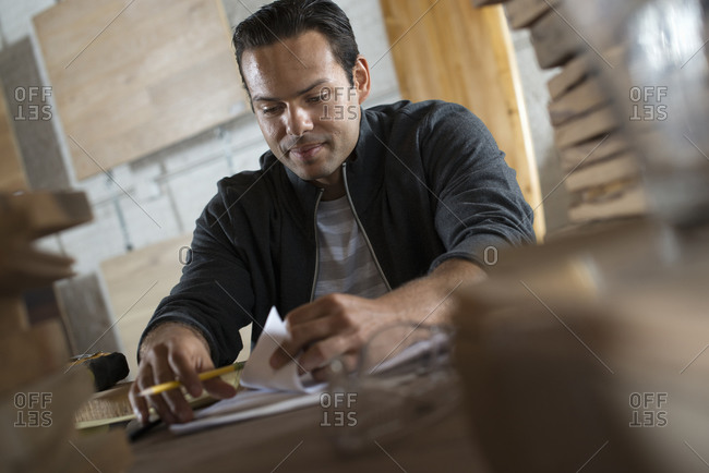 A young man in a workshop which uses recycled and reclaimed lumber to create furniture and objects. Using paper and pen to keep records.