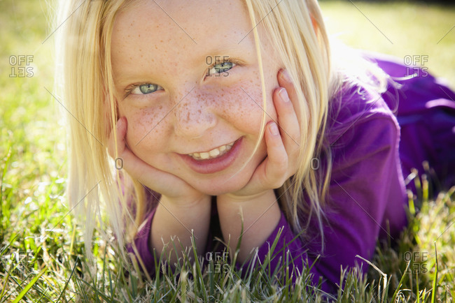 Young girl lying on the grass chin resting on her hands