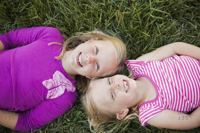 Two sisters lying on the ground and smiling
