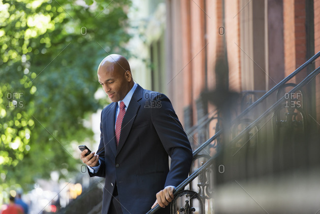 Businessman checking his phone on his way to work