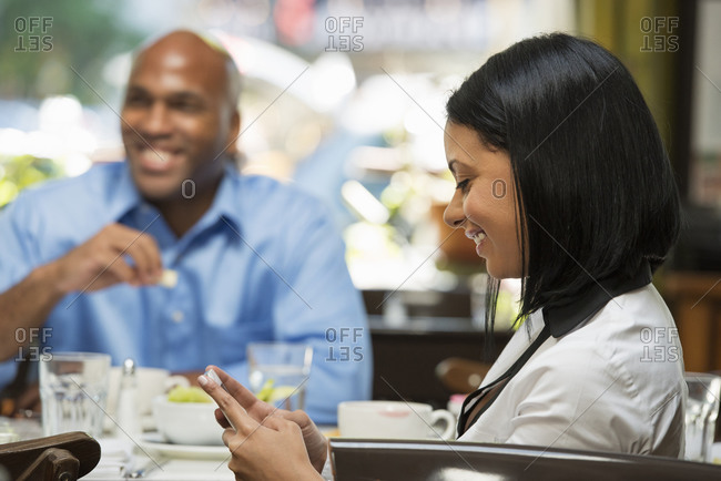 Woman checking her phone at table with colleagues