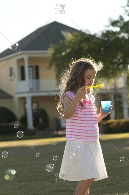 Girl blowing soap bubbles in nature
