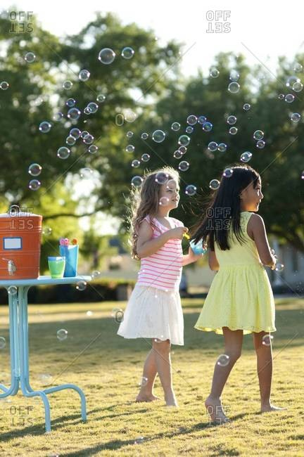 Girls blowing soap bubbles in the garden