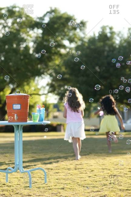 Girls running and blowing soap bubbles in the garden