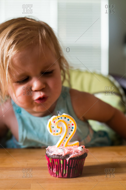 Cute little girl blowing out the candle