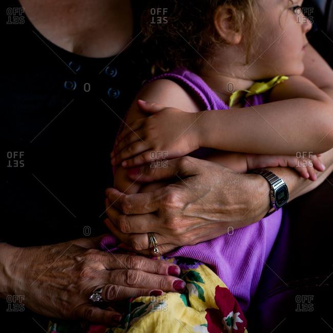Elderly woman hugging little girl