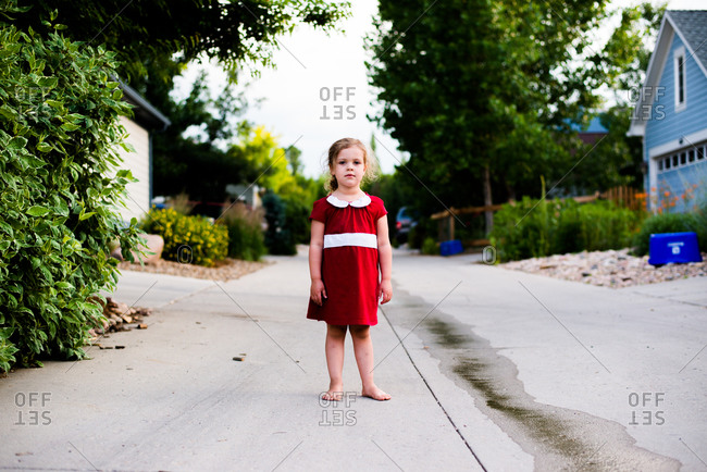 Girl standing barefoot on the street in red dress