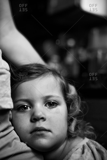 Worried girl being held by parent