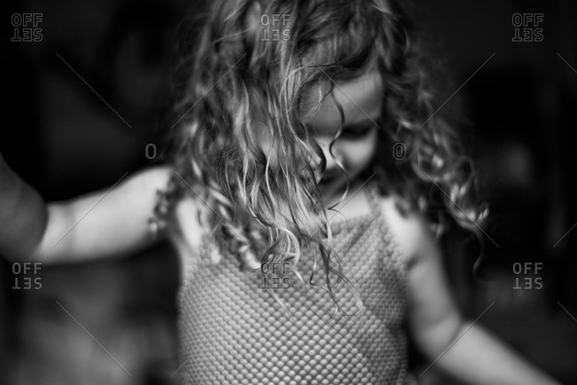 Little girl with curly hair wearing swimsuit