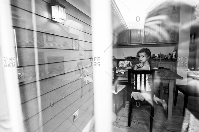 Little girl kneeling on chair in the kitchen