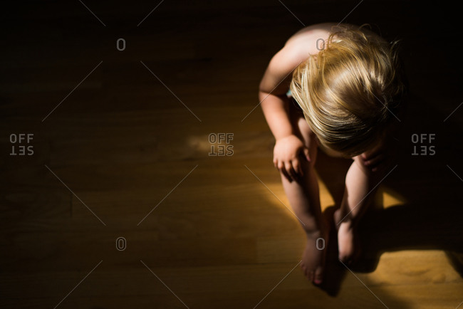 Overhead view of little girl sitting naked on the floor