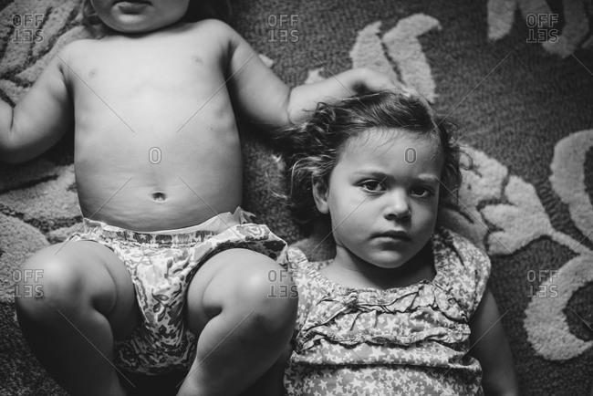 Overhead view of siblings lying on carpet