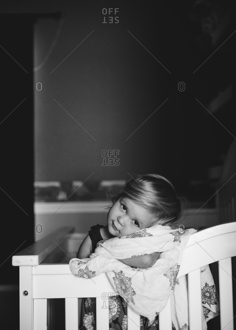 Cute girl with blanket standing in a crib
