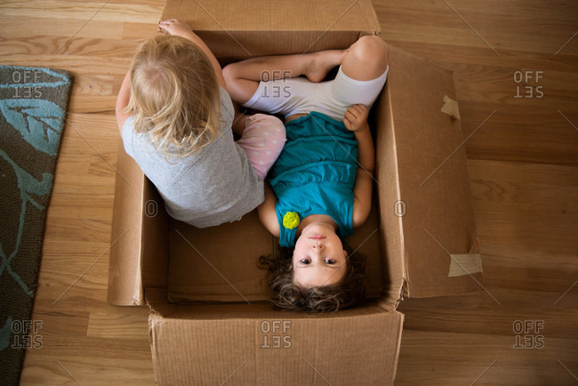 Overhead view of siblings sitting in cardboard box