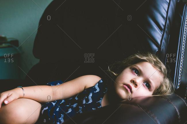 Girl lying in black leather armchair
