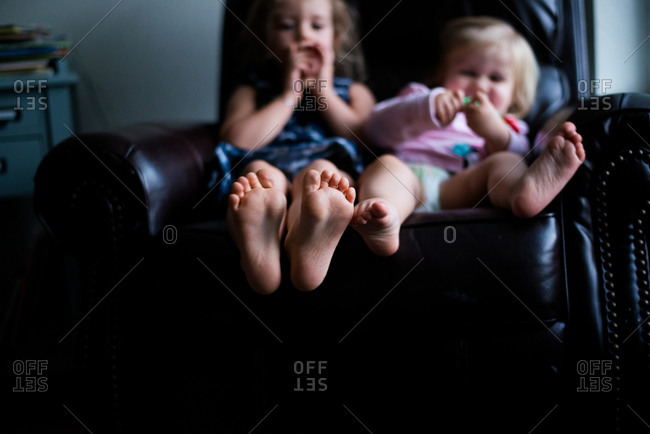 Siblings sitting in a leather armchair