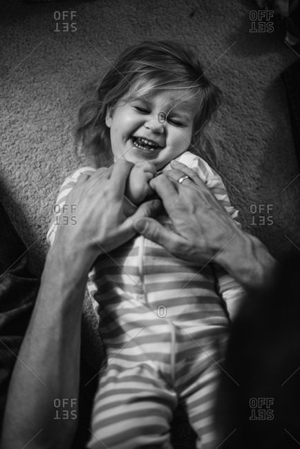 Parent tickling laughing girl