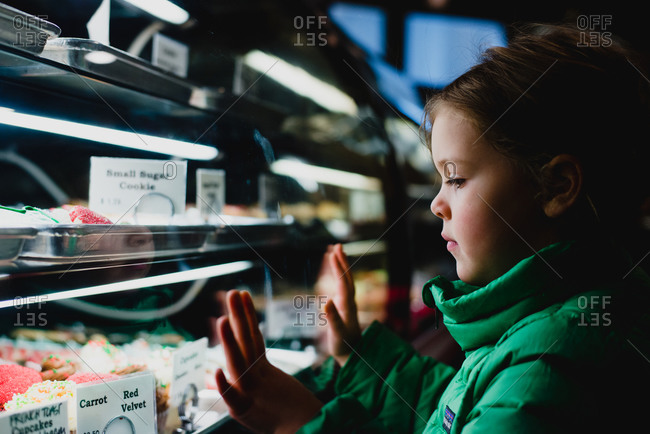 Side view of little girl choosing a cake at bakery