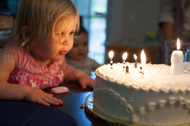 Cute little girl blowing out the candles