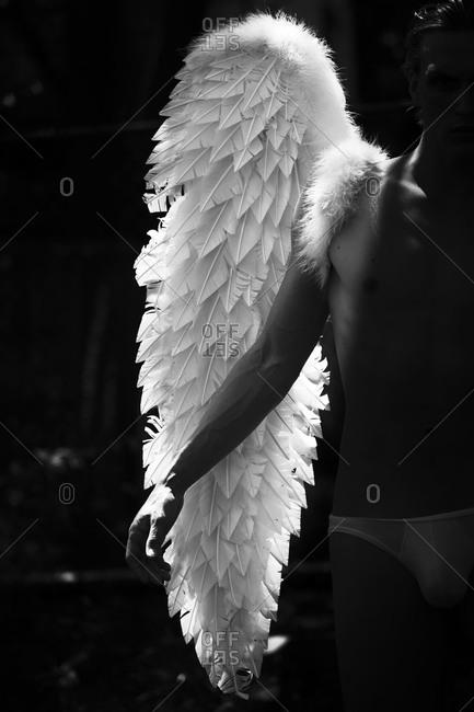 Man is underwear posing with angel wings