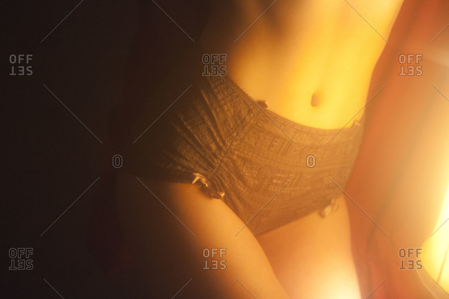 Woman's hips in panties illuminated by table lamp