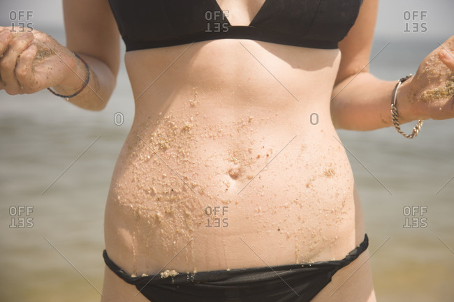 Woman's belly with sand on it
