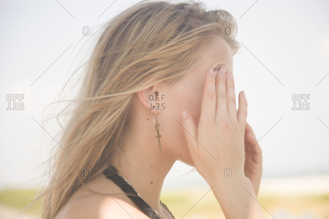 Woman standing in sunshine and touching her face
