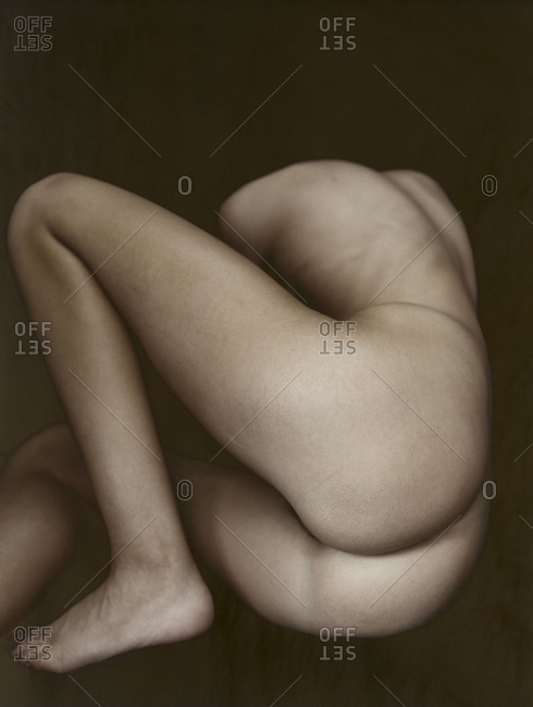 Rear view of naked woman lying