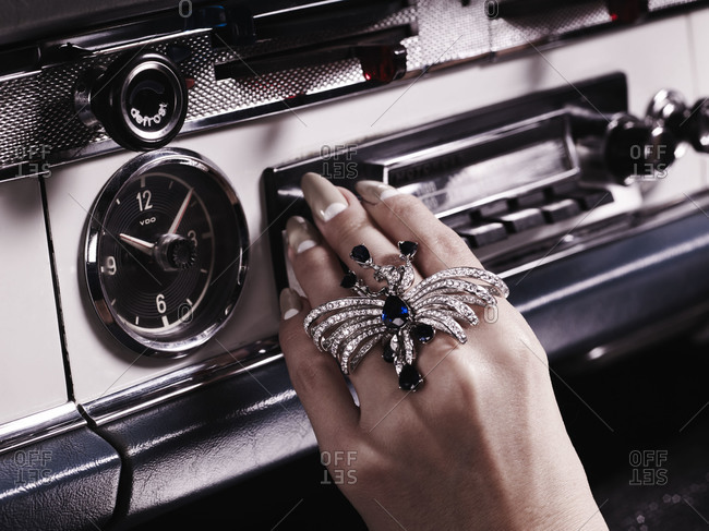 Hand of woman switching radio in car