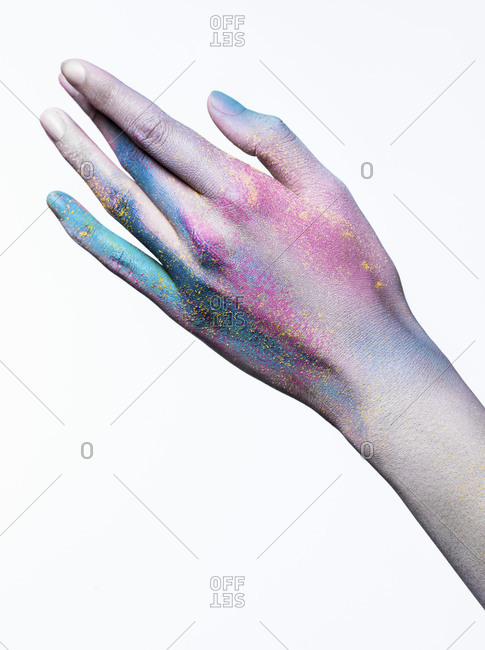 Hand of a woman painted with colorful powder