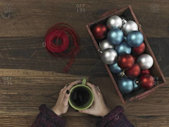 A collection of blue, red and silver ornaments and red ribbon in a box on a wooden board