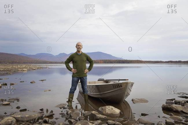 A man standing on a lake shore beside a small rowing boat