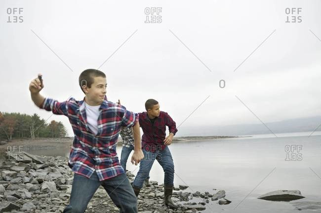 Three boys on the shore throwing skimmers pebbles across the water