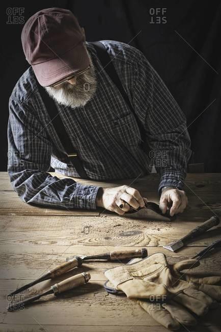 A man working in a reclaimed lumber yard workshop