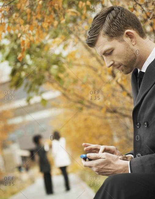 A man in the park checking a mobile phone