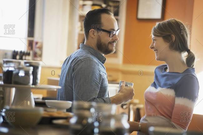 A couple sitting in a coffee shop smiling and talking over a cup of coffee
