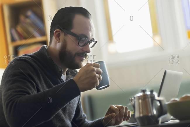 A bearded man having a drink of coffee