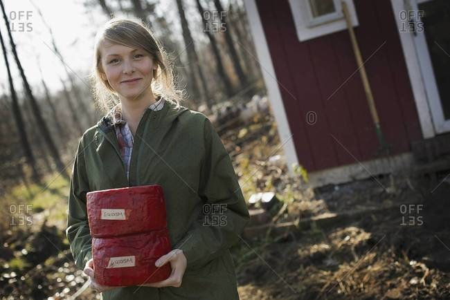 A young woman standing outside a dairy farm building holding two blocks of cheese