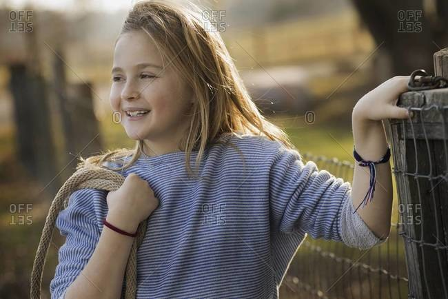 A young girl by a paddock fence