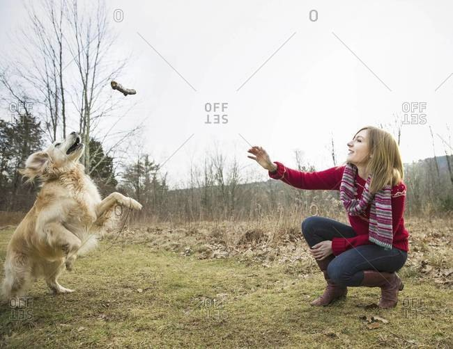 A young woman outdoors in the winter with a golden retriever dog