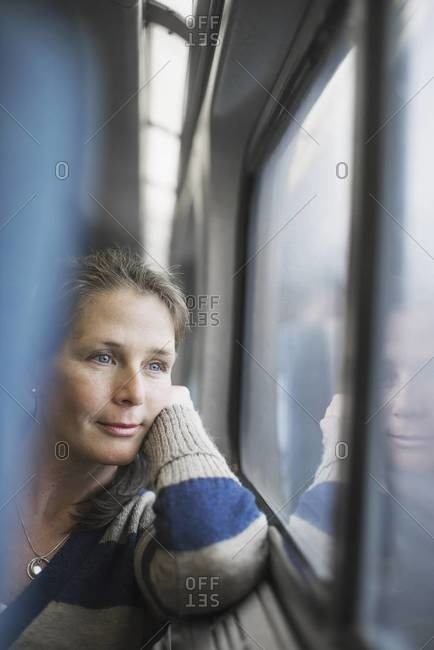 A woman sitting at a window seat in a train carriage, resting her head on her hand
