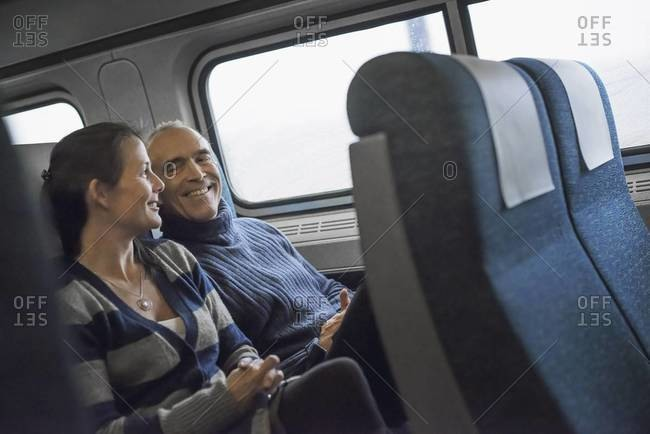 Two people sitting in a railway carriage, smiling