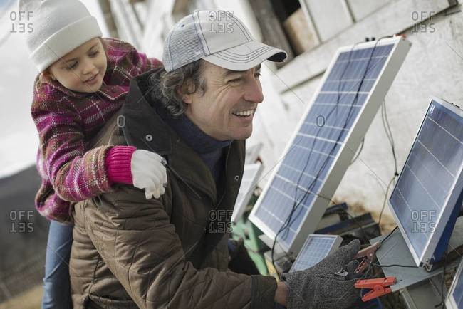 A man giving a child a piggybank while trying to connect the leads for solar power panels