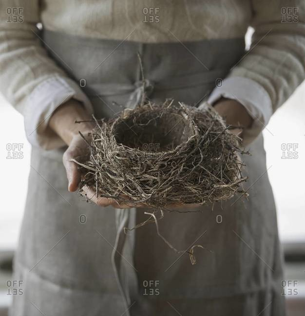 A woman in a work apron holding a woven twig bird nest