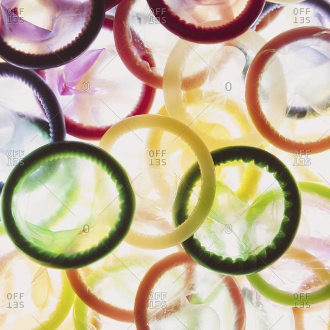 A large group of multi-colored condoms displayed on a white background