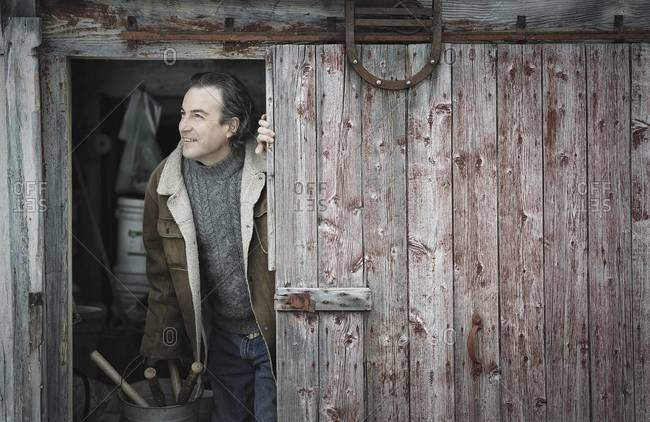 A man at an open barn door