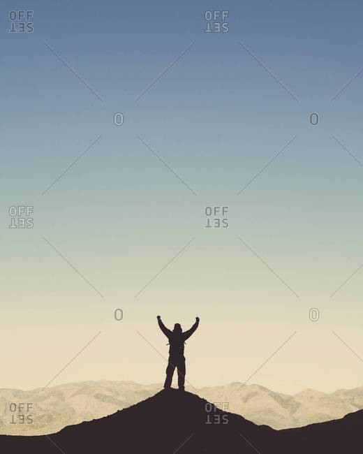 Silhouette of a male hiker wearing a backpack and standing on a hilltop in Death Valley national park