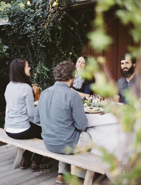 A group of people around a table in a garden