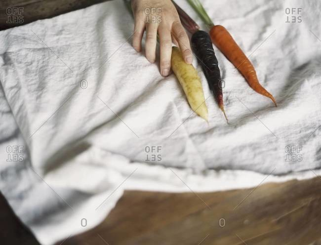 A person arranging fresh carrots on a white cloth